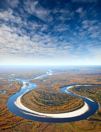 Aerial view of the river executing the loop during the cloudy day of autumn. Reklamní fotografie