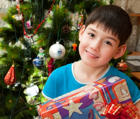 Happy boy with gifts in front of Christmas tree. Stock Photo
