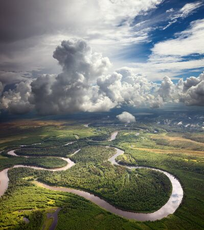 lowland: Aerial view of forest the river during summer day on background of great white clouds.