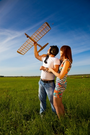 Young couple has holding the model airplane in their hands. They love each other and they are happy.