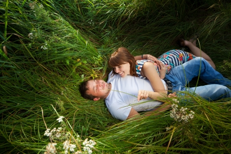 Young couple are lying in the grass. Girl and guy love each other. photo