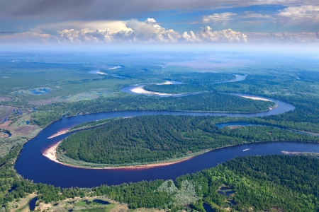Aerial view of forest the river during summer day on background of great white clouds  The ship with barge moves along the river