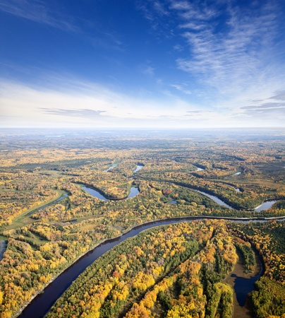 arial views: Aerial view of the forest under clouds during the autumn.