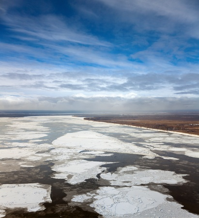 Aerial view of the great river with floating ice floes during the spring day. Drifting of ice.Driving of ice. Ice floe. photo