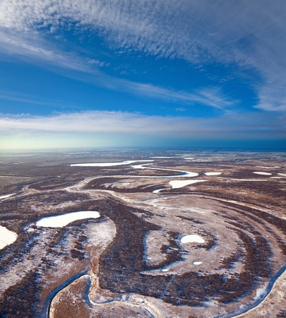 overhand: Aerial view of forest of plain and small river during a winter day.