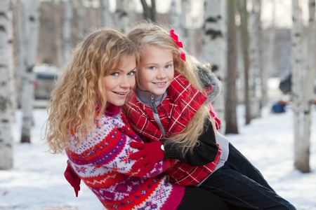 Mother and her daughter are sitting close each other in park in winter. They are happy and are smiling. photo