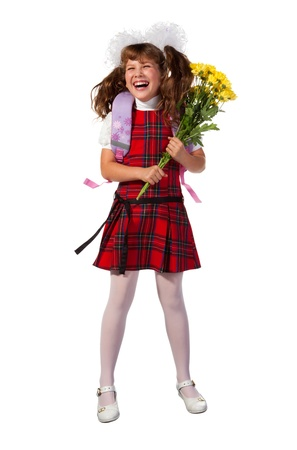 The girl is dressed in a school uniform fun laughs. She holds in her hands the yellow flowers. White ribbons are in her hair. photo