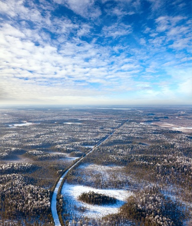 overhand: Aerial view of forest of plain and country road during a winter day.