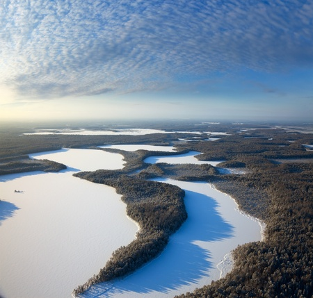 overhand: Aerial view of forest plain with lakes during a winter day.