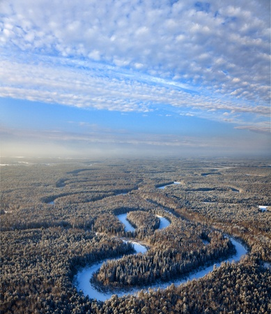 overhand: Aerial view of forest plain with small river during a winter day.