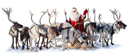 Kerstman in de buurt zijn herten in het tuig op de witte achtergrond. Hij heet u welkom en zwaait met zijn hand.