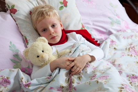 The little boy is sick. He lies in bed. Red scarf is on his neck. Teddy Bear is in his hand. Reklamní fotografie