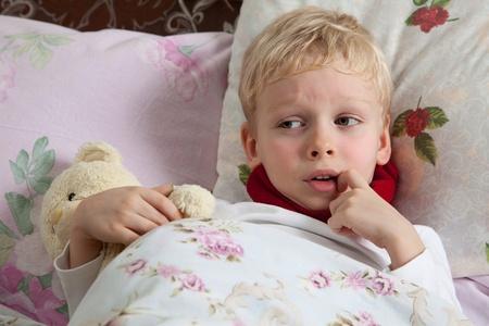 fiebre: El ni�o est� enfermo. Se tumba en la cama. Bufanda roja es en el cuello. Teddy Bear es en la mano. Foto de archivo
