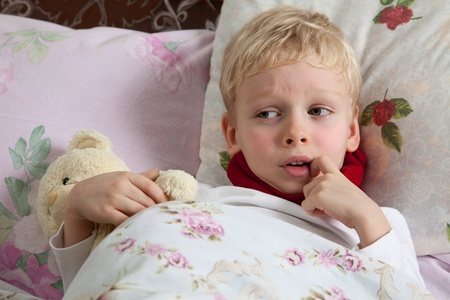 The little boy is sick. He lies in bed. Red scarf is on his neck. Teddy Bear is in his hand. Stock Photo