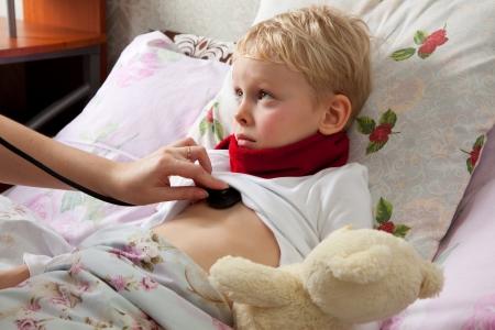 De kleine jongen is ziek. Hij ligt in bed. Rode sjaal is op zijn nek. Teddy Bear is in zijn hand. Iemand ontdekkingsreizigers jongens longen met een stethoscoop.