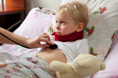 The little boy is sick. He lies in bed. Red scarf is on his neck. Teddy Bear is in his hand. Somebody explorers boys lungs with a stethoscope. Stock Photo