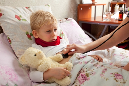 explores: The little boy is sick. He lies in bed. Red scarf is on his neck. Teddy Bear is in his hand. Woman explores boys lungs with a stethoscope.