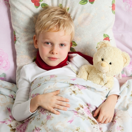 Sick boy is laying in bed with his teddy bear. Them temperature are measured thermometer. Stock Photo
