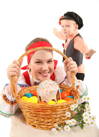 russian easter: Cheerful children are dressed in Russian national dresses. Girl holds the basket with Easter eggs and a holiday cake. Boy is dancing.