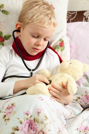 stethoscope boy: Sick boy is doing examination health for teddy bear with a stethoscope. Stock Photo
