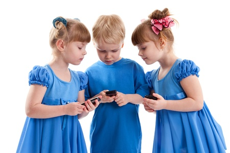 Two girls which are twins and a boy are sending messages or are playing on their cell phones on white background. They dressed in blue. Stock Photo - 17361991