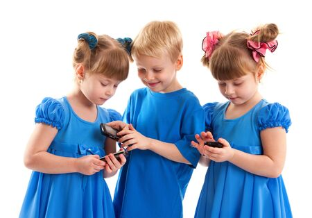 Two girls which are twins and a boy are sending messages or are playing on their cell phones on white background. They dressed in blue. Stock Photo - 17361994