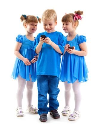 Twee meisjes die zijn tweelingen en een jongen zijn het verzenden van berichten of spelen op hun mobiele telefoons op een witte achtergrond. Ze gekleed in blauw.