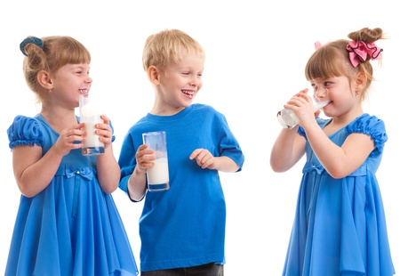 Little girls-twins and boy are drinking milk of glasses in their hands and are laughing on white background. Stock Photo - 17361992