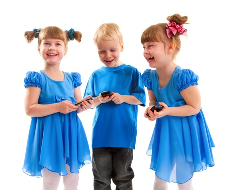 Two girls which are twins and a boy are sending messages or are playing on their cell phones on white background  They dressed in blue  Stock Photo - 17413971
