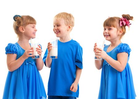 Little girls-twins and boy are drinking milk of glasses in their hands and are laughing on white background  Stock Photo - 17453747