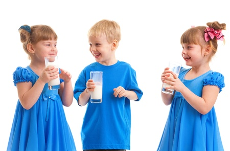 Little girls-twins and boy are drinking milk of glasses in their hands and are laughing on white background Stock Photo - 17453745