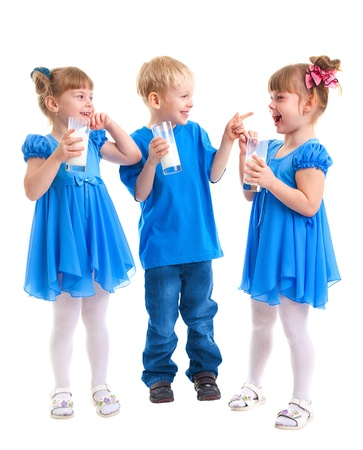 Little girls-twins and boy are drinking milk of glasses in their hands and are laughing on white background  Stock Photo - 17453746