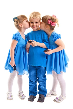 Two girls which twins are kissing a boy which is sending messages or is playing on his cell phone on white background. All they dressed in blue. photo