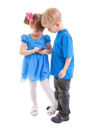 Girl and a boy are sending messages or are playing on his cell phones on white background. They dressed in blue. Stock Photo - 17455046