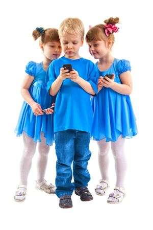 Two girls which are twins and a boy are sending messages or are playing on his cell phones on white background. They dressed in blue. Stock Photo - 17622003