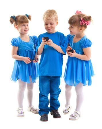 Two girls which are twins and a boy are sending messages or are playing on his cell phones on white background  They dressed in blue Stock Photo - 17621985