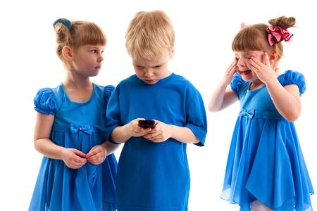 fille pleure: Deux jeunes filles qui sont jumeaux et un gar�on envoient des messages ou jouent sur ses t�l�phones cellulaires sur fond blanc Banque d'images
