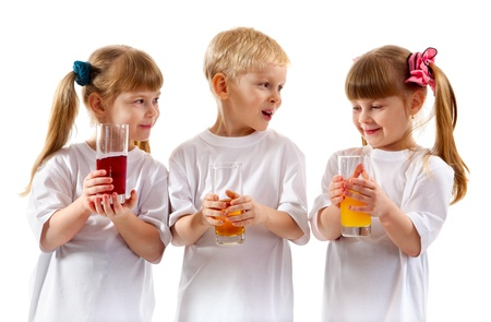 Little girls-twins and boy are holding juice of glasses in their hands and are laughing on white background. photo