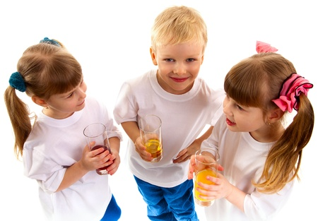 Little girls-twins and boy are holding juice of glasses in their hands and are laughing on white background. They communicate with each other. The boy smiles and looks straight. photo