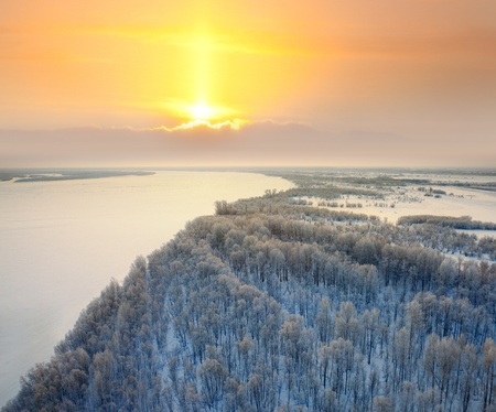 sunny cold days: Forest on the bank of great river during winter sundown. Stock Photo