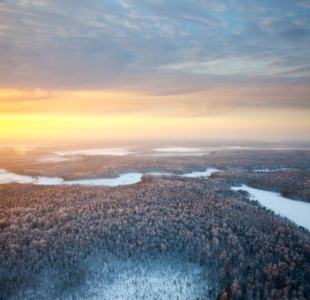 The Aerial view of snow-covered forest in time of sunny winter evening. Crowns of coniferous trees are lighted up by a bright setting sun. photo
