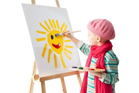 Vrolijke kleine jongen staande op de schildersezel. Jonge kunstenaar houdt in zijn handen het palet met verf. Hij schildert de zon. Stockfoto