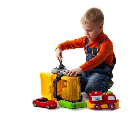 Little cute boy repairing a plastic toy truck. Isolated on white. photo