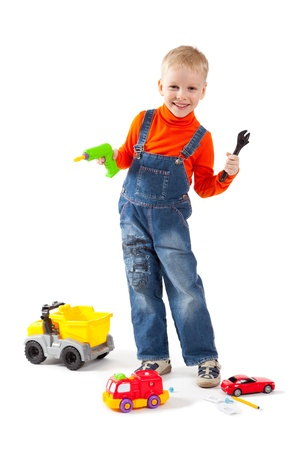 Little cute boy repairing a plastic toy truck. Isolated on white.