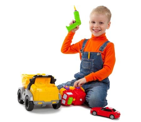 Weinig leuke jongen herstellen van een plastic stuk speelgoed vrachtwagen geïsoleerd op wit Stockfoto