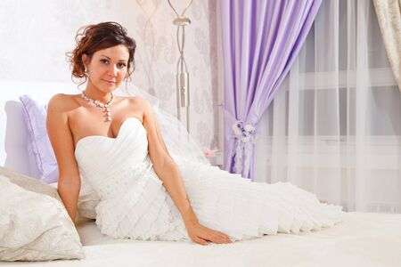 Bride is sitting on bed in hotel room  photo