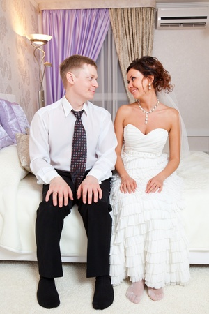 The bride and groom are sitting on the bed in the hotel  It photo