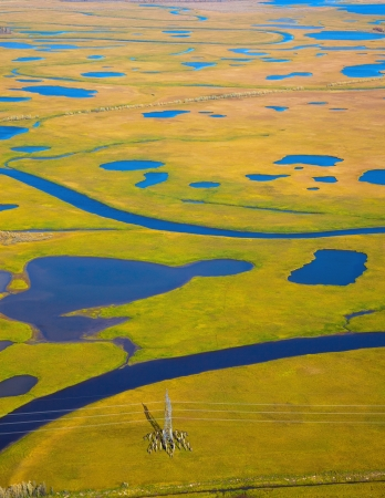 Aerial view of the tundra in the autumn. Impassable plain was crossed by some rivers and lakes. Power line is going through the valley. Banco de Imagens