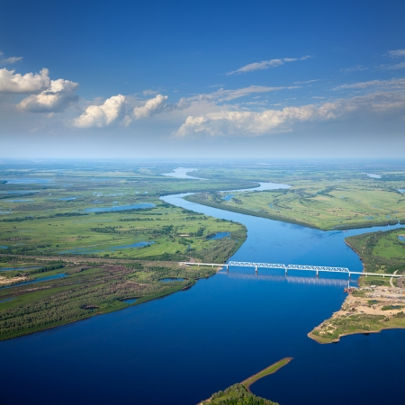 aerial animal: Aerial view of the river and the railroad bridge under the white clouds in the summer.