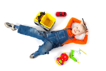 Little cute boy repairing a plastic toy truck on white background